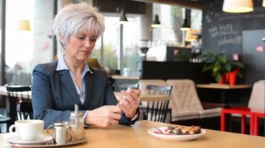 Middle aged woman works on smartphone in cafe - coffee and cake — Stok video