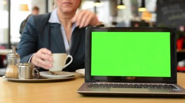 Notebook (computer) green screen - middle aged woman drinks coffee in cafe — Stok video