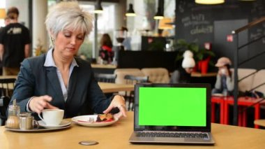 Notebook (computer) green screen - middle aged woman drinks coffee in cafe and smiles to camera — Stok video