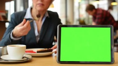 Tablet green screen - woman eats cake and drinks coffee in cafe — Vídeo Stock