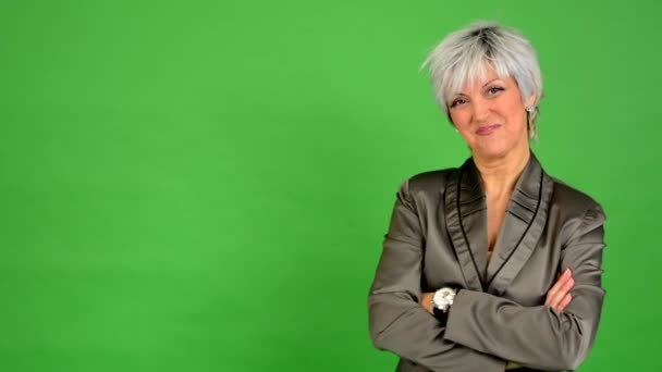 Business middle aged woman smiles (fold arms) - green screen - studio — Vídeo de stock