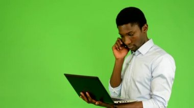 Young handsome black man works on notebook and phone - green screen - studio — Stock Video