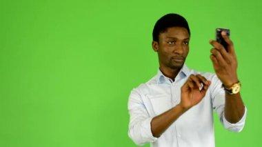 Ung snygg svart man fotograferar med smartphone - grön skärm studio — Stockvideo