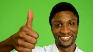 Young handsome black man shows thumb on agreement - green screen - studio - closeup — 图库视频影像