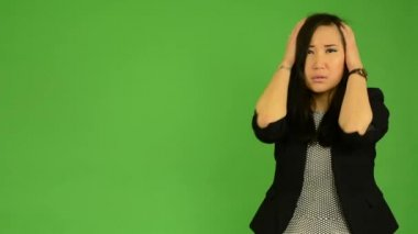 Young attractive asian woman is afraid - green screen studio — Stockvideo