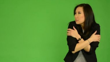 Young attractive asian woman shivers - cold - green screen studio — Stock Video