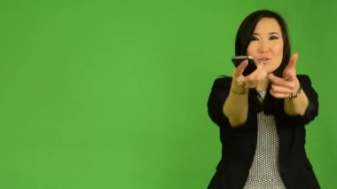 Young attractive asian woman dances with smartphone - green screen studio — Stok video