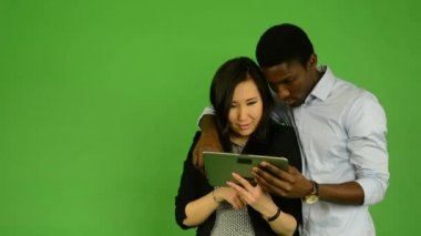Happy couple work on tablet and smile to camera - black man and asian woman - green screen studio — Stockvideo
