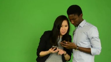 Happy couple work on smartphone and smile to camera - black man and asian woman - green screen studio — Stok video