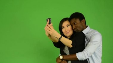 Happy couple take photo - black man and asian woman - green screen studio — Stock Video