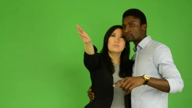 Happy couple point to the distance (sightseeing) - black man and asian woman - green screen studio — Stock Video