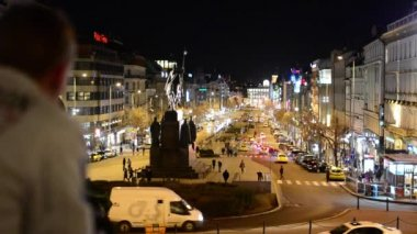 Man looks on night Wenceslas Square with people and passing cars - buildings and lights — Stock Video