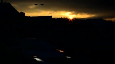 Sunset over the city - silhouette - road with cars (headlights) - timelapse — Stockvideo