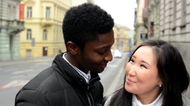 Happy couple smile to camera - black man and asian woman - urban street with car - closeup — Stock Video