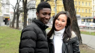 Happy couple show thumb on agreement - black man and asian woman - urban street with cars - city — Stock Video