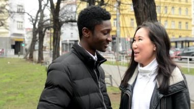 Happy couple laugh and talk (conversation) - urban street with cars in the city - park - black man and asian woman — Stock Video