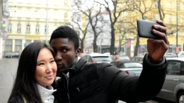 Happy couple take photo - black man and asian woman - urban street with cars - city — Stock Video