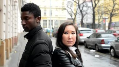 Unhappy couple are offended - black man and asian woman - urban street with cars - city — Stock video