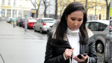 Young attractive asian woman works on smartphone - urban street - city — ストックビデオ
