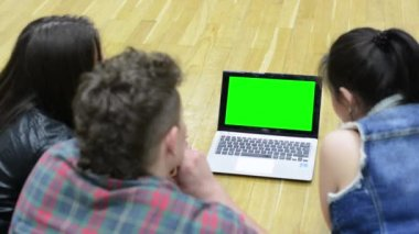 Group of three friends (dancers) work on computer (notebook) - green screen - two women and one man - floor — Stock Video