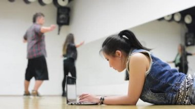 Young asian attractive woman work on computer (notebook) - two friends (dancers) dance in background - hall — Stock Video