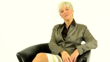 Business middle aged woman goes to sit down and smiles - white background - studio — Stock Video