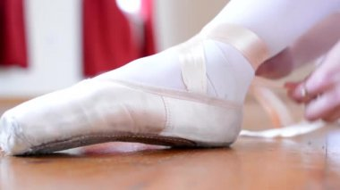 Young ballerina preparing for dance - ballerina ties shoes - closeup (detail) — Stock Video