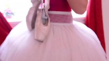 Ballerina carries ballet shoes over shoulder - interior - red curtain — Stock Video