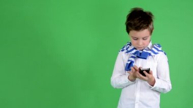 Young handsome child boy works on smartphone (text messaging) - green screen - studio — Stock Video