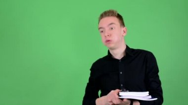 Young handsome man holds textbooks tired - green screen - studio — Stockvideo