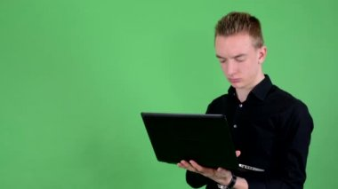 Young handsome man works on notebook - green screen - studio — Stock Video