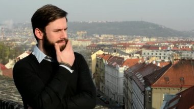Young handsome man with full-beard (hipster) thinking and look around - city in background — Stock Video