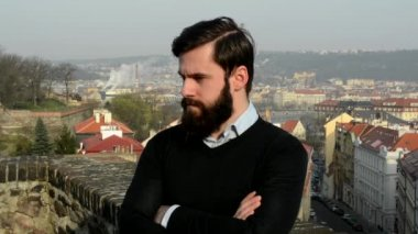 Young handsome man with full-beard (hipster) looks around and thinking (serious face) - city in background — Stockvideo