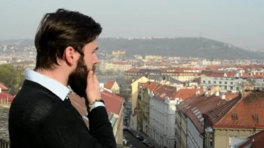 Young handsome man with full-beard (hipster) look at the city and meditates - city in background — Stock Video