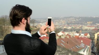 Young handsome man with full-beard (hipster) takes photos of city with smartphone - city in background — Wideo stockowe