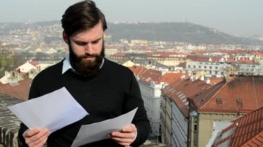 Young handsome man with full-beard (hipster) reads documents - city in background — Stock Video