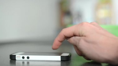 Man works on a mobile phone - typing message - kitchen units — Vídeo stock