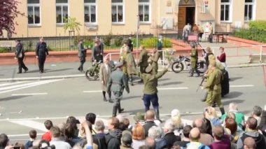 PRAGUE, CZECH REPUBLIC - MAY 2, 2015: reenactment performance battle of World War II on the street - the enemy(german) suddenly kills captain - soldiers shooting at each other - audience (viewer) — Stock Video