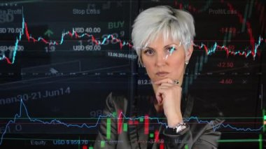 Business middle aged woman looks to camera (thinking) - financial market (exchange) - graph — Stock Video