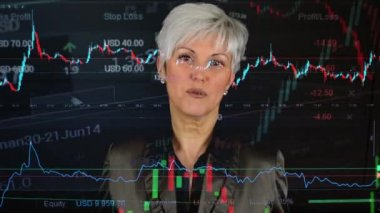 Business middle aged woman talks to camera (interview) - financial market (exchange) - graph — Stock Video