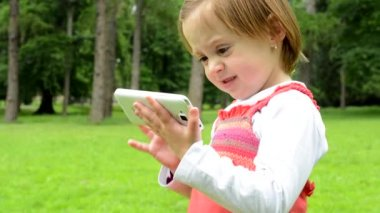 Young little girl works on smartphone - park — Stockvideo