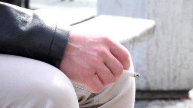 Man smokes a cigarette on the street - closeup — Stockvideo