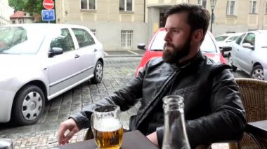 Young handsome hipster man sitting in restaurant (outdoor seating) and smoking - street (parked cars) - beer — Stockvideo