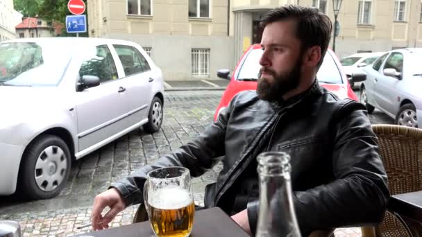 Young handsome hipster man sitting in restaurant (outdoor seating) and smoking - street (parked cars) - beer — Vídeo de stock