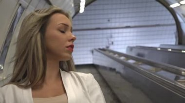 Young attractive blonde woman travels on the escalator in the subway — Stockvideo