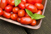 Tomatoes With Basil In A Wooden Bowl On Floorboards — 图库照片