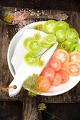 Slices of green and pink tomatoes on a white plate — Photo