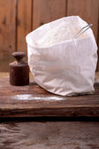 Bag of whole flour on wooden background — Stock Photo