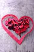 Heart shape made of red lace ribbon on a wooden table — Stock Photo
