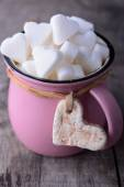 Pink mug with sugar hearts — Stock Photo
